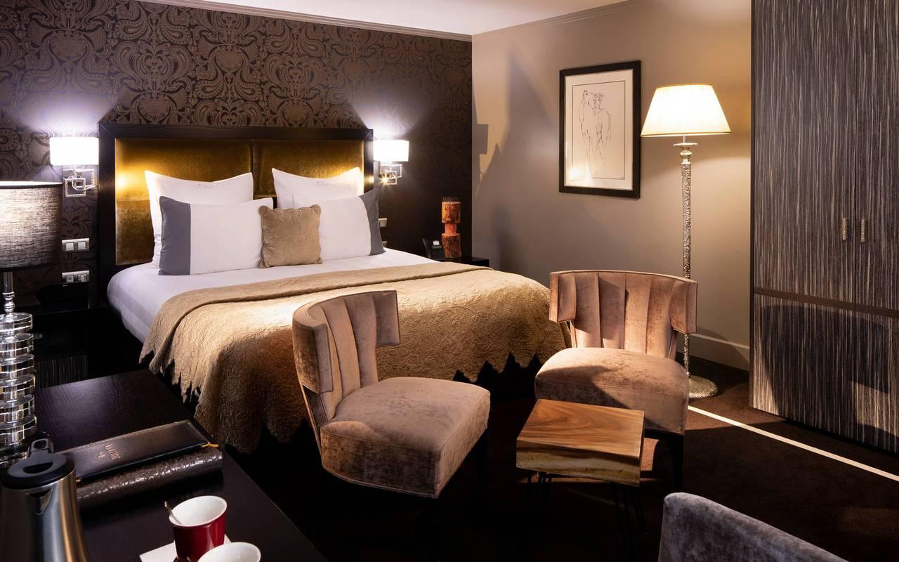 Un grand lit double confortable avec deux fauteuils, hotel de luxe paris, Juliana Hotel Paris.