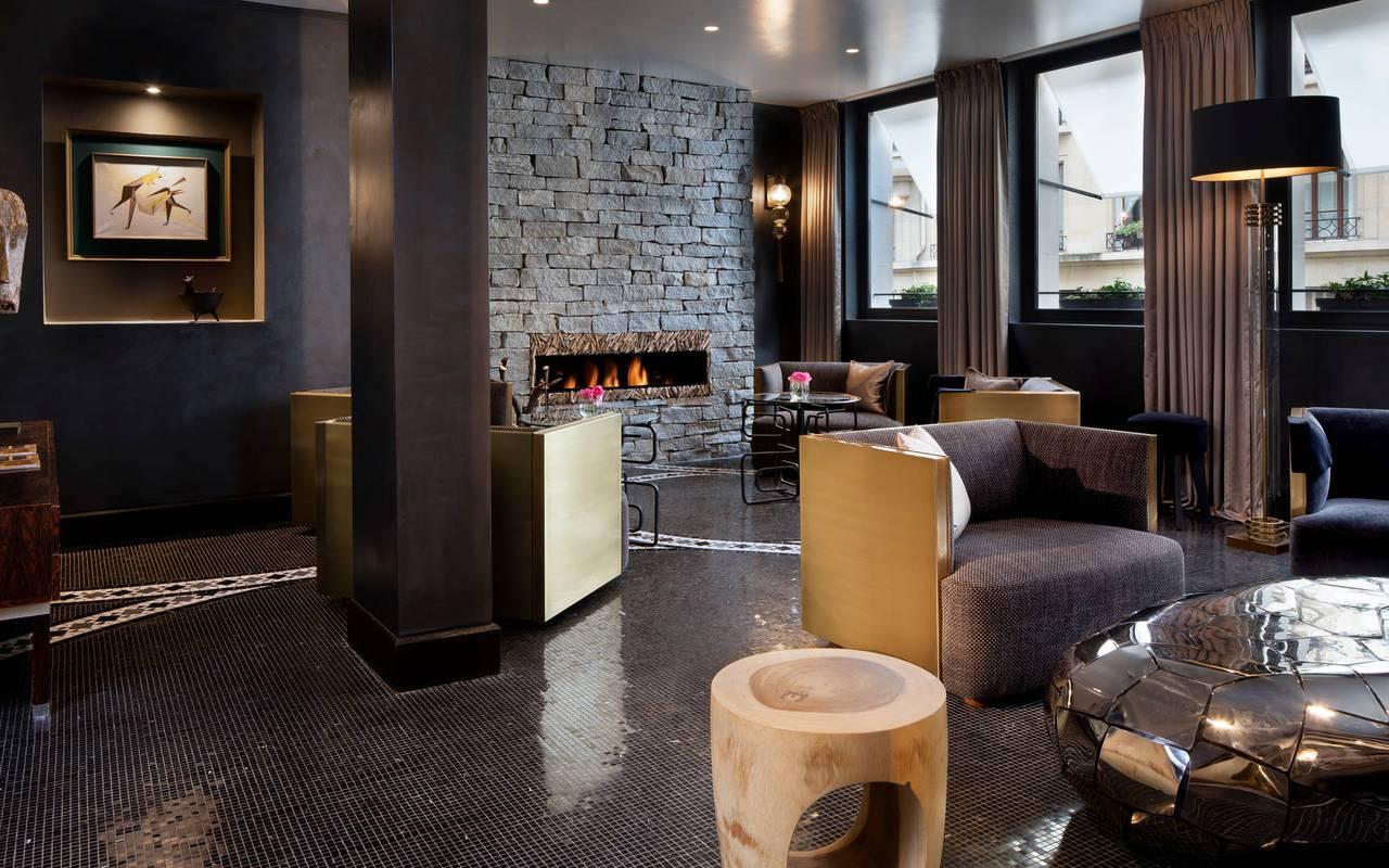 Salon cosy avec feu de cheminée et fauteuils, hotel vue sur la tour eiffel, Juliana Hotel Paris.